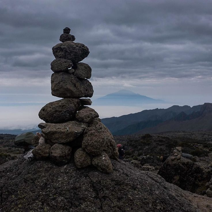 Cairns like this are everywhere on Kilimanjaro! Everyone wants to leave their mark on the mountain. This image shows Mount Meru in the background.  #kilimanjaro #mountains #tanzania #sunset #love #africa #trekking