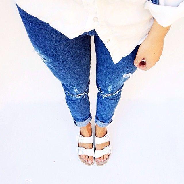 White Birkenstocks, distressed jeans.