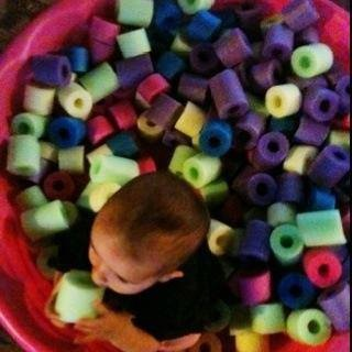 Buy a cheap kiddie pool and fill it with cut up pool noodles for a makeshift ball pit.