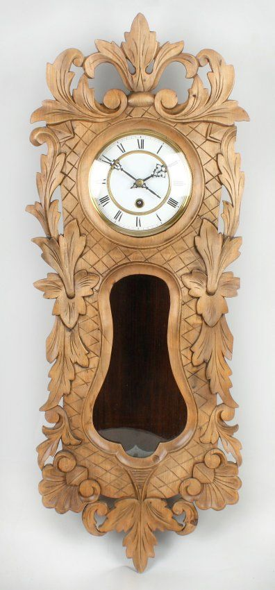 "A Black Forest carved fruitwood wall timepiece. Having a 5"" white enamelled Roman dial. The single-train movement with winged stamp in a profusely carved case with lattice incised ground, glazed dial window and lenticle. 30.5"" (77.5cm) high"