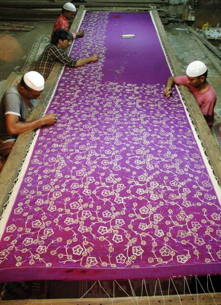 reiminister:    Indian Muslim artisans work on a handembroideredsilk saree (traditional Indian women's outfit) at a workshop in Hyderabad, southern India, October 4, 2006. Artisans make specially designed sarees on order for customers to wear them during the Muslim holy month of Ramadan. Specially designed sarees are priced up to 50,000 Indian Rupees (1,094 USD). Photo by Noah Seelam.