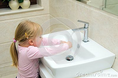 A small girl washing her hands in a basin under running water.