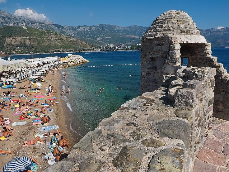Sun worshipers flock to Pizana Beach in Budva, Montenegro, a small but popular beach tucked into a protected cove beneath the walls of the old city