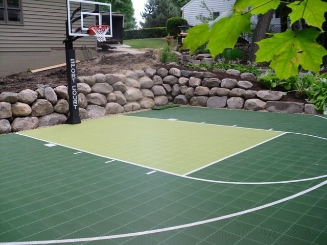 Sport court with boulder retaining wall http www for Sport courts for backyards