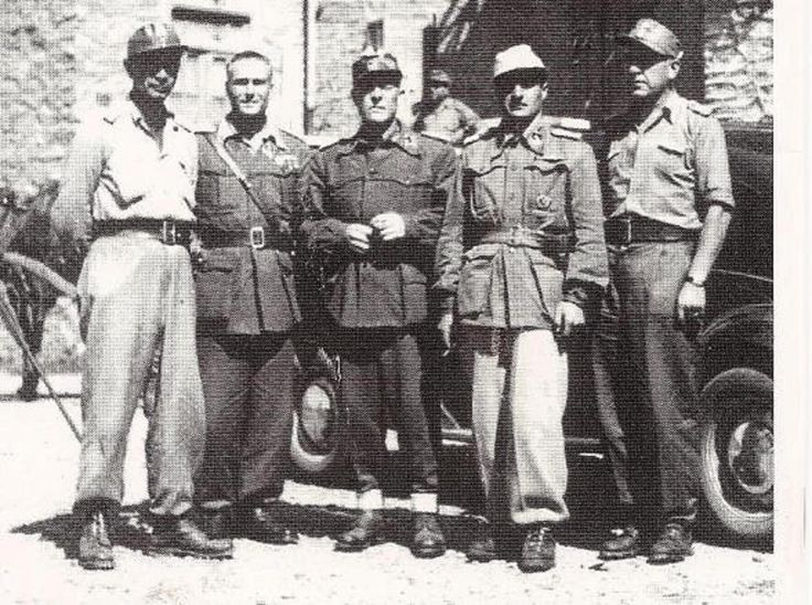 Carlo Federigo degli Oddi (center)and Italian SS Officers. All wear different styles of uniforms and shirts. Oddi is wearing a collared sahariana jacket in wool. Also seen is a sahariana in tropical cloth to his left. Wool collarless sahariana to his right. The Officers on the ends are wearing shirts bearing shoulder boards. Most wear a version of a brimmed field hat similar to a German M43 or Italian M42.