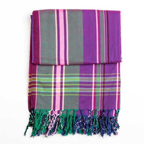 Traditional Kenyan Kikoy. Handwoven out of 100% Cotton in Purple and Green. Kikoys can be used as scarves in the Winter, as Shawls in the Spring, Beach Towels in the Summer and all around the house in the Autumn - a beautiful multi-use must-have accessory! ----- About the brand Love'edu: Lov'edu Living was founded by Ibiza raised Anna Boettcher in 2013 in London. Today, Lov'edu is both a physical and an online ethical store that offers unique interior decoration, accessories, jewellery and…