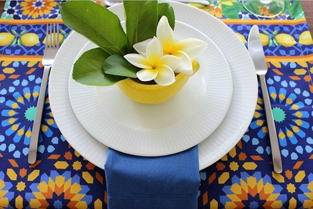 mesa posta com jogo americano estampado em azul e amarelo com prato branco e vaso de limão siciliano com flores.