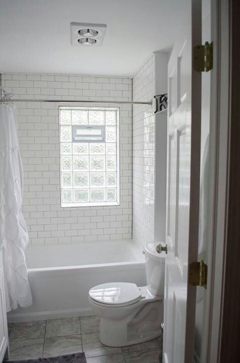 We remodeled! White subway tile, gray grout, glass block window.