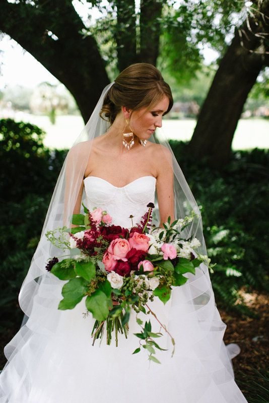 bride's lush, loose and wild summer bouquet of pink romantic antique garden roses, red charm peonies, burgundy astilbe, burgundy scabiosa, pink ranunculus,white majolica spray roses, white larkspur, fern, jasmine vine, lemon leaf. crepe myrtle and seeded eucalyptus.
