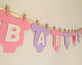 **Cute and adorable banner for baby showers!!**  This banner is a perfect touch for baby girl showers!   Alternating Blush Pink and Pastel Green onesies and letters are made of high quality heavy cardstock paper and strung on ivory satin ribbon using mini wooden clothespins. Sparkling Silver Heart design in the middle adds a little elegance to the cute pink and green color theme. All BABY GIRL letters and the center heart design are mounted with pop-dots, adding that special something with a…