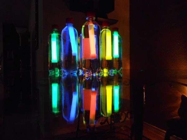 Un bowling maison avec des bouteilles en plastique et des bâtons lumineux