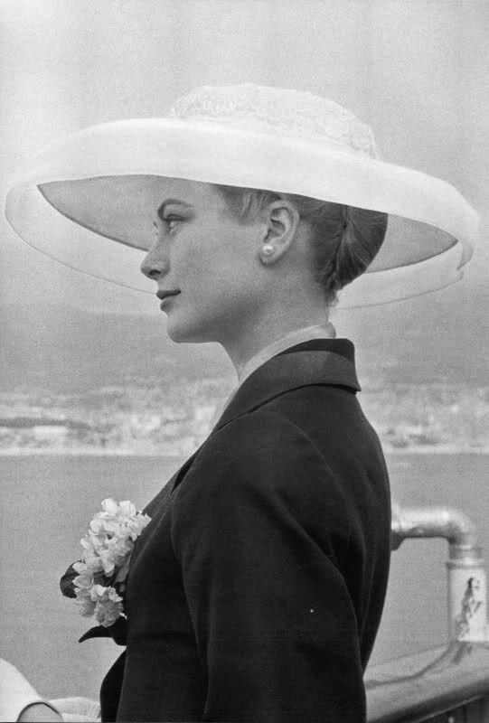 Grace Kelly 's arrival in Monaco for her marriage to Prince Rainier. She wore a navy coat ensemble by Ben Zuckerman.