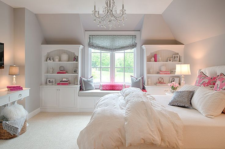 Gorgeous girl's bedroom features a white crystal chandelier hung from tall ceilings over gray walls which frame white built-in bookcases on either side a window seat reading nook topped with gray and pink pillows below a window dressed in a gray roman window shade.