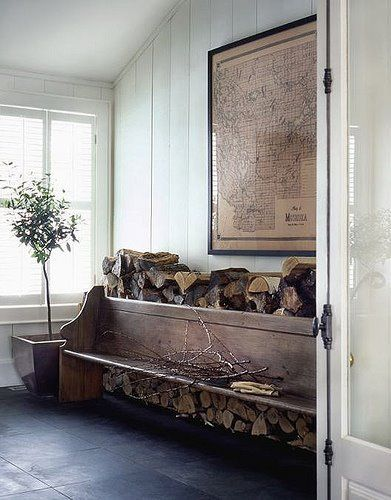 A cozy mudroom with a reclaimed wooden pew and stacked fire wood, staying warm in Maine