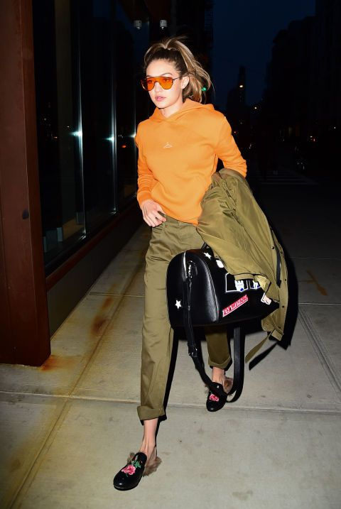 Out and about in New York, Gigi continues her undercover matching streak with an orange hoodie, nails, and tinted sunglasses. Gucci slides and a weekender complete the look.