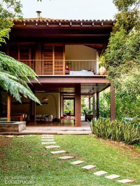Em meio a natureza a casa moderna de madeira tem telhado colonial e mostra integração total com o ambiente. A valorização de portas que podem ser abertas totalmente aumenta a proximidade e permite uma visão linda do campo.