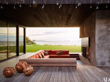 The Long Island home of Lyor Cohen and Xin Li embraces its majestic setting on Noyack Bay with numerous outdoor spaces, including this sunken fireplace area with built-in seating | archdigest.com