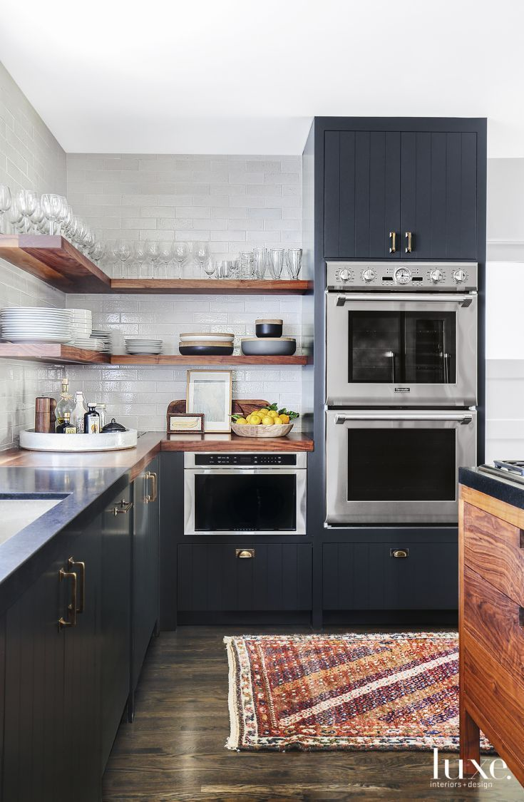 The completely gutted kitchen includes cabinetry designed by Alexander wearing hardware from Liz's Antique Hardware; integrated Thermador appliances are from APD. Wooden shelves pop against a white tile backsplash from Ann Sacks. The vintage kilim from Mehraban brings pleasing contrast.