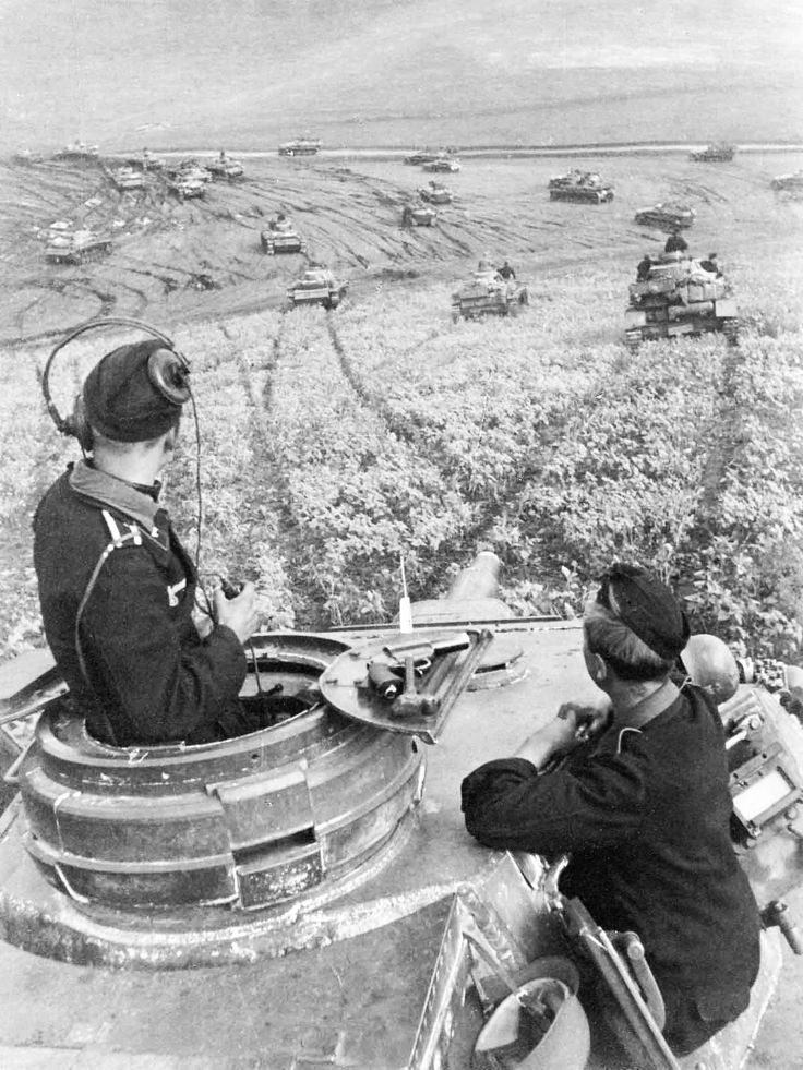 An impressive view of the commander and gunner of a Panzer IV tank as part of an armored unit moving across the Russian steppe toward a road in the distance at the base of a shallow valley. Note the flare gun on the right hand hatch lid. Robust and reliable, the Panzer IV saw service in all German combat theaters, and it was the only German tank to remain in continuous production throughout the war from 1936 to 1945. It even saw combat with Syrian forces in the Six Day War of 1967.