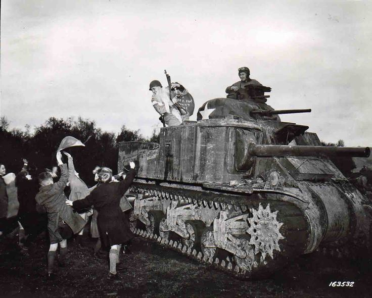 U.S. Army Sergeant Hiram Prouty dressed as Santa Claus carrying an M1928 Thompson submachine gun in an M3 General Lee tank entertains British children at Christmastime in Perham Downs, United Kingdom (December 5, 1941).