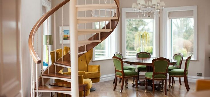 Home renovation with antique dining chairs and a bespoke spiral staircase. Designed by Missi Gray Interior design.