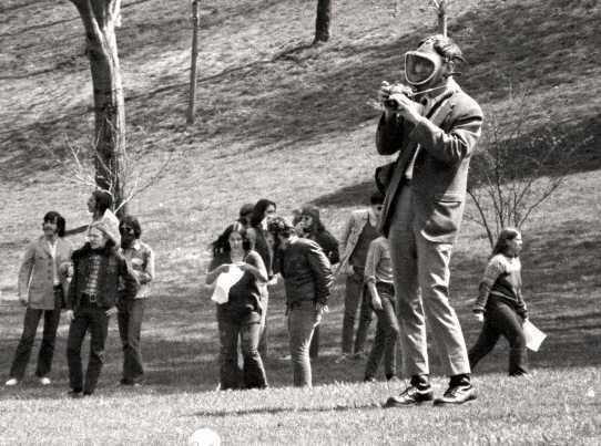 Terry Norman, in mask, takes pictures of the May 4, 1970, antiwar demonstration on the Kent State University campus before the shootings that day. Though Norman was highly visible during the protest, he has remained a shadowy figure in the events. The girl holding a white rag near her chest in the background is Mary Vecchio,
