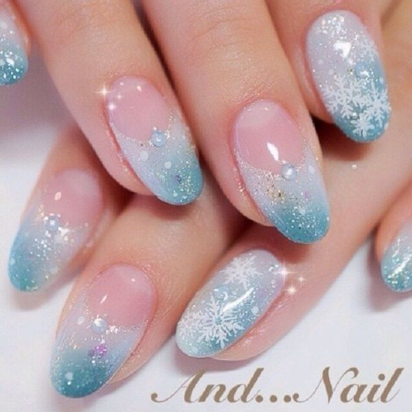 Crystal blue French tip snowflake nail art design. Give more sparkle to your French tip by giving it the gradient effect of white to crystal blue. Add embellishments on top to make it look like it's fresh from the snow outside.
