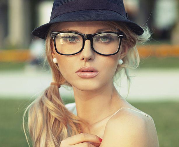 Ragazza bionda con cappello nero e occhiali da vista