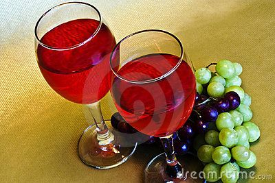 Two glasses of red  wine and two bunches of grapes