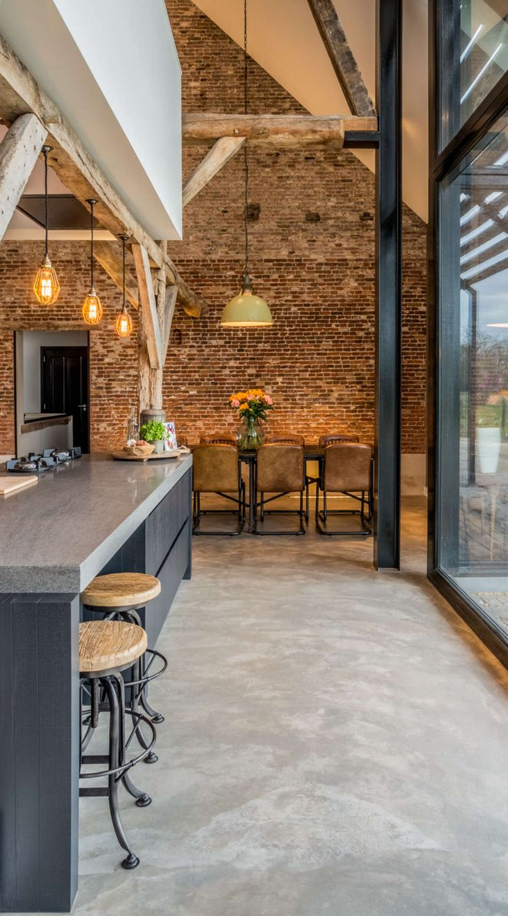 Old farmhouse converted into a warm industrial farmhouse with view of an old brick wall, and original wooden beams.