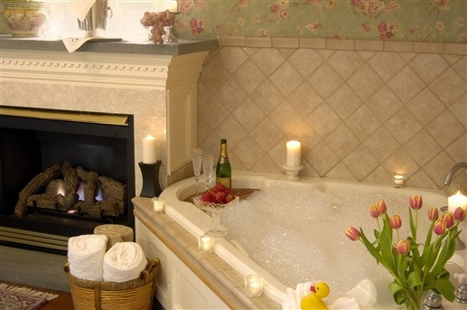 The Garden Cottage at Arrowhead Inn Bed and Breakfast in Durham, North Carolina has a fireplace next to the whirlpool tub