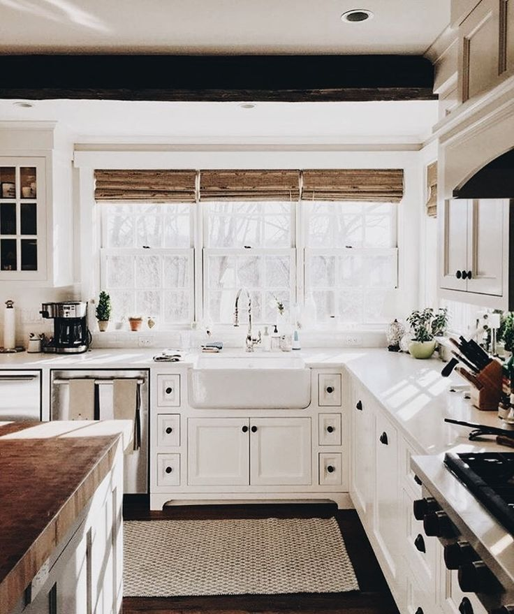 Perfection! The inclusion of matchstick window treatments and wood countertops really warms up this white space.