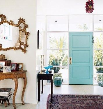 love the tension between the modern door and windows and the vintage mirror and furniture