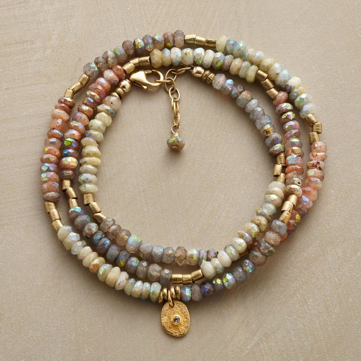 "WARM GLOW BRACELET -- 238.00 A unique three wrap bracelet, in which labradorite, sunstone, brass and subtly iridescent mystic aquamarine circle your wrist while an 18kt gold vermeil disk, sparked with topaz, shines like the sun. 14kt gold-filled clasp. USA. Exclusive. Fits 6"" to 7"" wrists."