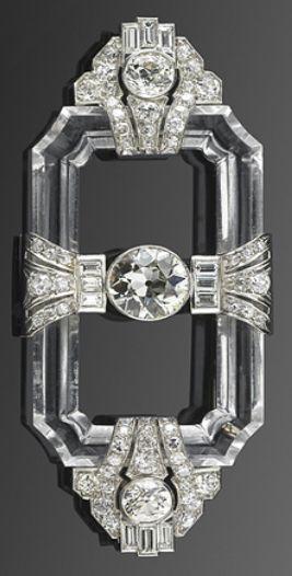 An Art Deco brooch, circa 1920s. A rock crystal frame connects platinum set geometric motifs centring upon an old European cut diamond. #ArtDeco #brooch
