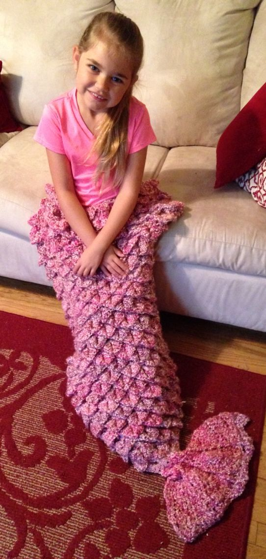"""Cozy blanket makes her mermaid dreams come true! Pocket keeps her toes warm while she cuddles on the couch! Designed with crocodile stitch to resemble the mermaid's """"scales"""" with a variegated pattern."""