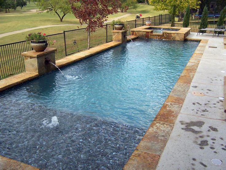 Straight line pool in Las Colinas with Tanning ledge, lions head water features, exposed beam and raised spa with glass tile