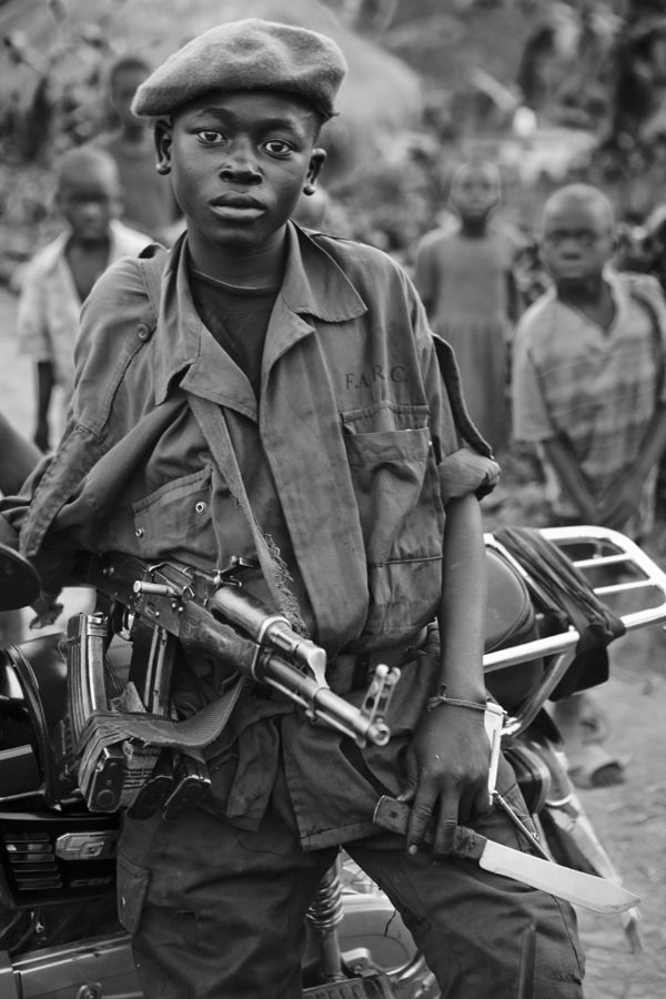 An African child soldier is holding his AK47 rifle with a knife in his hand…
