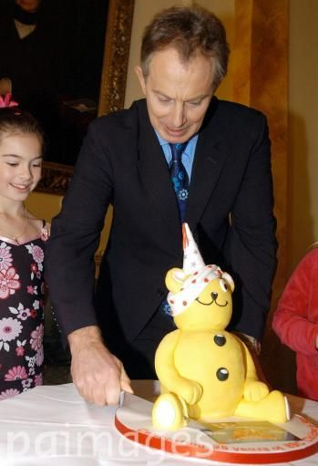 British Prime Minister Tony Blair cuts the Children in Need cake while Frances Martin from Chesterfield looks on, during a visit by 10 children, who have been helped by BBC Children in Need, to Number 10 Downing Street. The visit heralds the start of a day of fundraising around the UK for BBC Children in Need.