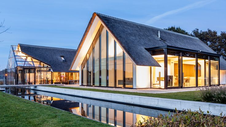 A gabled greenhouse appears to slide out from beneath the thatched roof of this villa, completed by Maas Architecten in the Dutch countryside