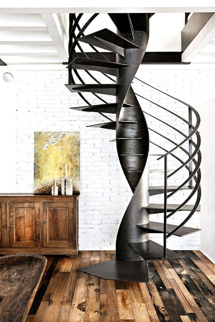 Metalowe spiralne schody w kontrascie z drewnianą podłogą
