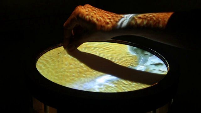 Screens as they exist today are flat, 2D and rigid; even the 3D displays we have today are not true 3D - they are optical illusions. We created a 2.5D display that is shape changing with the help of actuators, depth cameras, projector and a silicone screen. 'Obake' (o-baa-keh) as we lovingly call it, imagines how we would interact with elastic display. We could literally pinch and pull them!  Create mountains by pulling them out of the screen, draw rivers with your fingers, elevate an ...
