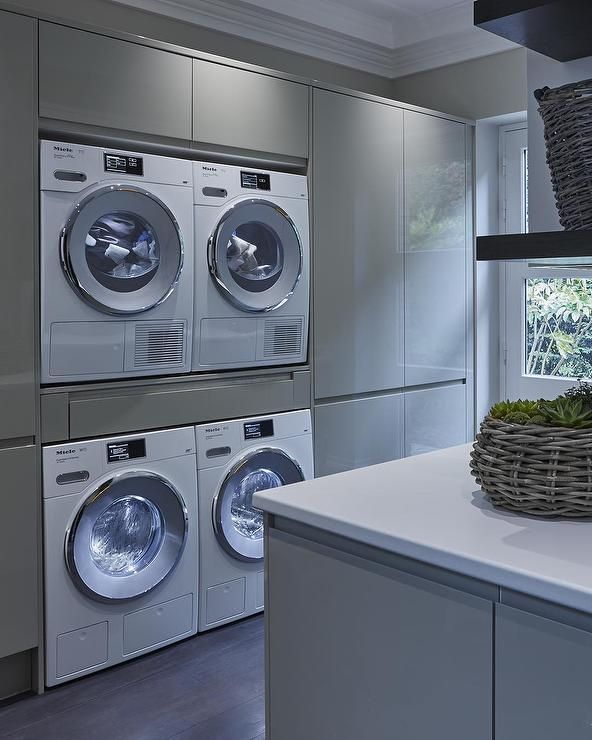 Modern laundry room features glossy gray lacquered cabinets fitted with two sets of washers and dryers facing a gray laundry room island.