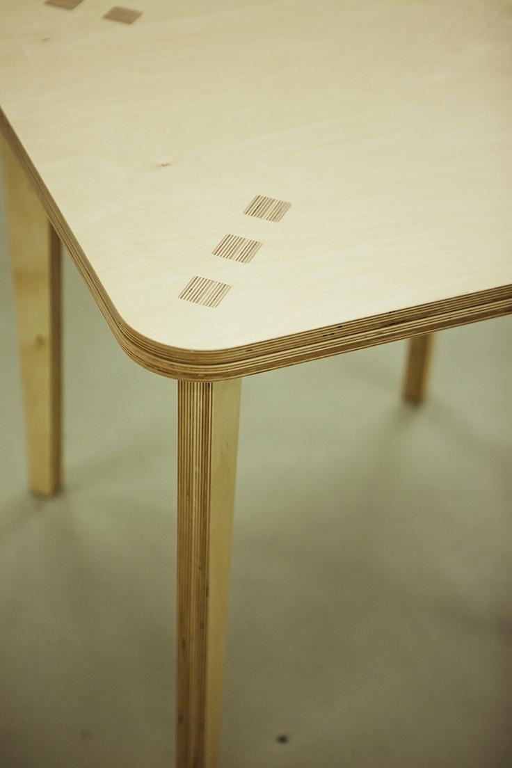 Combina Cookie Table - Masa de bistro pentru patru persoane. Foloseste o singura foaie de placaj multistratificat. Este asamblata fara niciun element metalic. Picioarele (dispuse la 45 de grade, pentru o buna stabilitate) se imbina cu blatul si formeaza la suprafata acestuia o retea de 12 patrate cu aspect de intarsie.  Partea inferioara a blatului este decupata pentru a reduce masa si pentru a crea o zona perimetrala utila la deplasarea mesei.  Placaj multistratificat de mesteacan