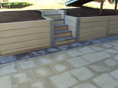 Retaining wall steps made out of two types of concrete sleepers. The siding shown here would be perfect for the stepped/tiered retaining wall garden bed.