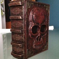 Altered book by Alma. An ordinary book, a skull added (made out of clay molded on to the book cover), then covered in tissue paper and painted with acrylic paint.