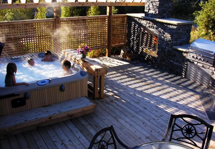 Enjoy the beauty of your custom outdoor fireplace while you relax in the tranquility of your outdoor hot tub. #fireplace #custombackyard