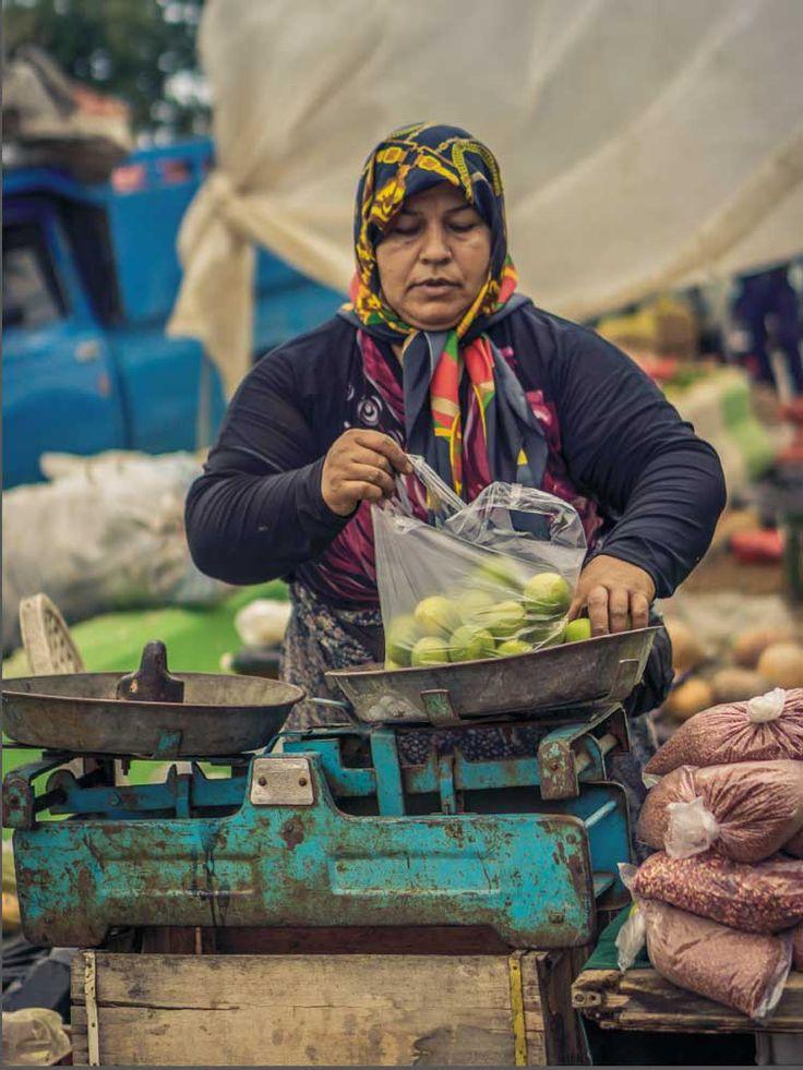 Local grocer in a farmers market near the Caspian sea, selling beautiful, fresh limes.