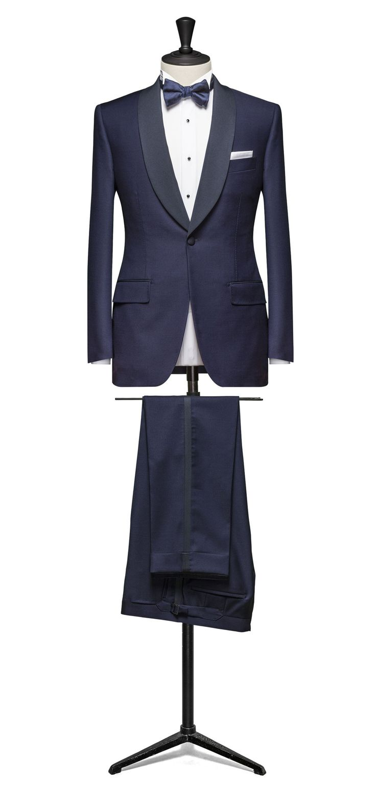 Midnight blue dinner suit. A classic shawl collar dinner suit in a light weight midnight blue wool with a classic 1 button style jacket. Styled with a classic lapel & side vents Teamed with a white dress shirt and navy bow tie. A choice of linings to and trims are available 2 piece made to measure from £795 3 piece made to measure £925 Please contact us to arrange a made-to-measure appointment to discuss your individual requirements.