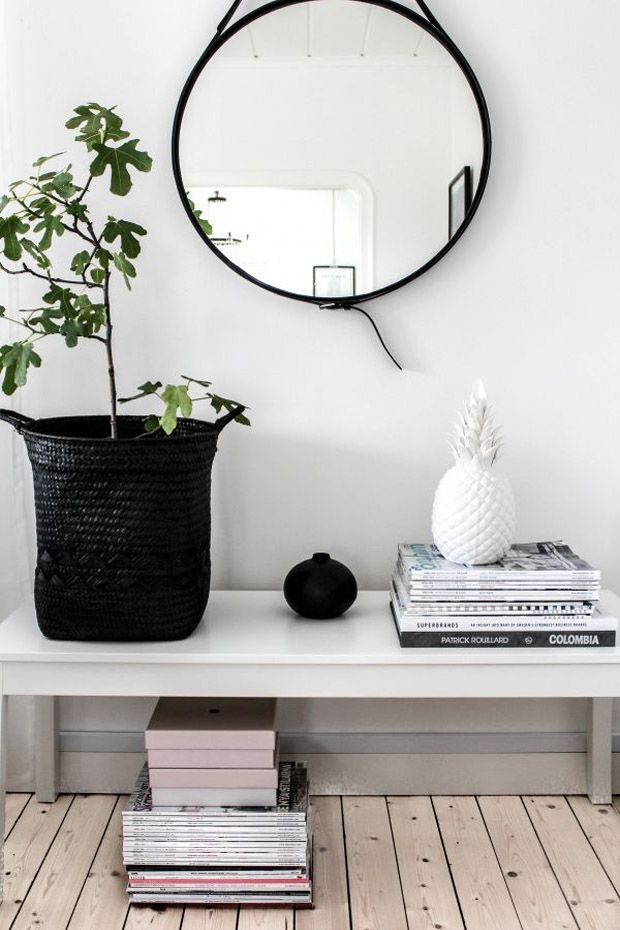 Entry:  White on white with pops of black from mirror and basket.  Stacked books with accessories on top add interest and symmetry.